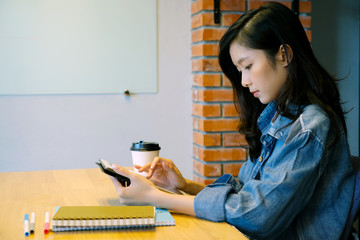 Young asian woman using digital tablet at home office background, casual office life, Asian female and digital tablet while working at home, People and technology concept