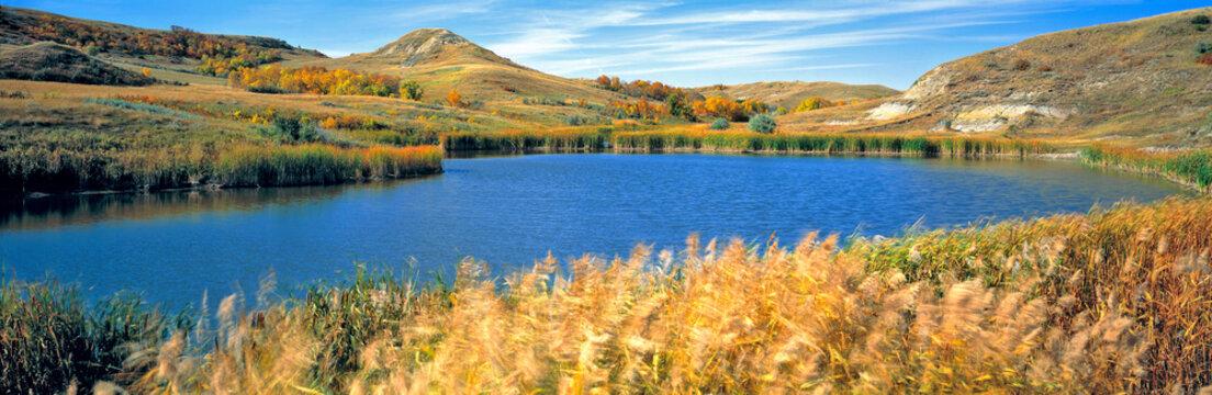 USA, North Dakota, Lewis & Clark SP. Autumn light slants over this deep blue pond in Lewis & Clark State Park, North Dakota