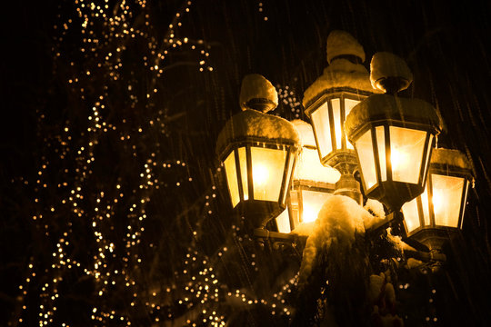 USA, Washington, Leavenworth. Snow-covered street lamps at night during Christmas holiday.
