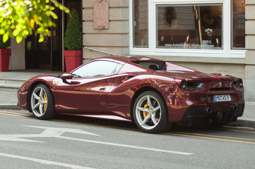 red ferrari 488 parked in the street in front of luxury Hotel