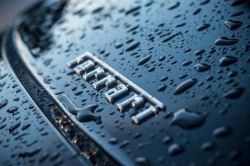 closeup of rain drops on black ferrari logo
