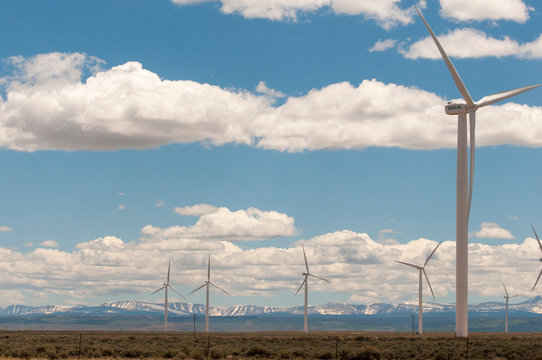 USA, Wyoming. Wind farm between Rocky Mountains and interstate.