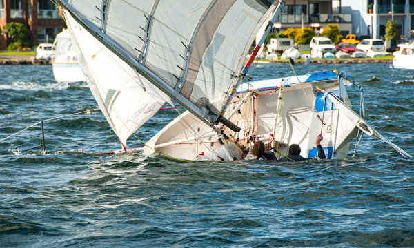 Two children in the water climbing back into a capsized sailboat.