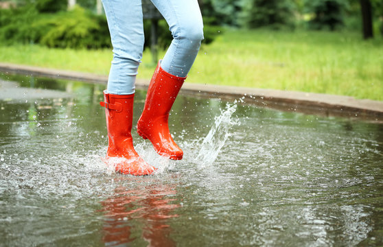 Woman with red rubber boots jumping in puddle, closeup. Rainy weather