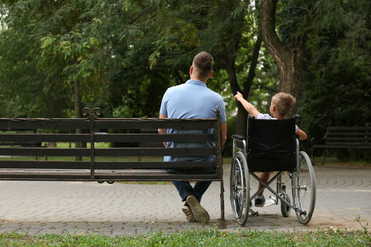 Father with his son in wheelchair at park