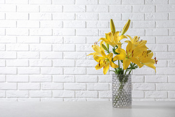 Glass vase with yellow lily flowers on marble table near white brick wall, space for text