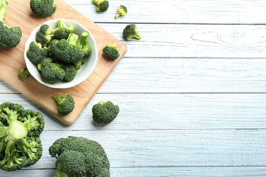 Flat lay composition of fresh green broccoli on white wooden table, space for text