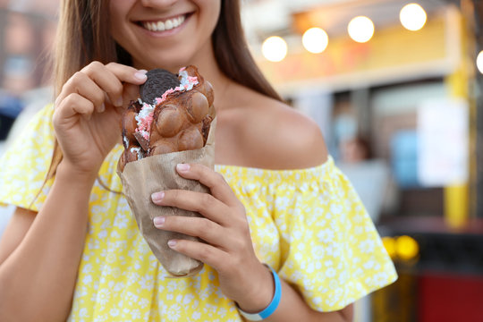 Young woman holding delicious sweet bubble waffle with ice cream outdoors, closeup