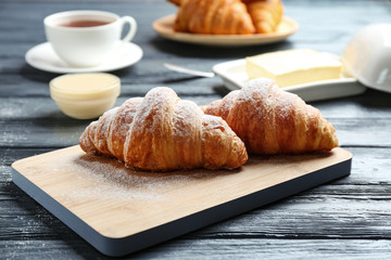 Board with tasty croissants on dark wooden table. French pastry