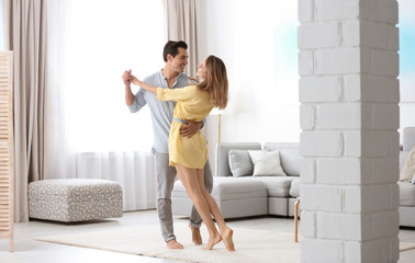 Beautiful young couple dancing in living at home