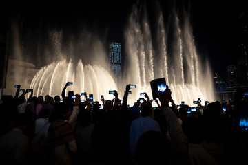 Tourists take pictures of the singing fountains