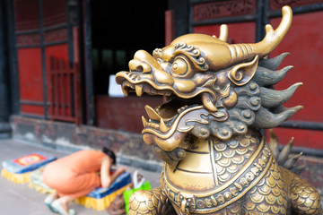 Head of a golden Lion statue at Wenshu monastery and blurred Chinese woman praying kneeling in background in Chengdu China