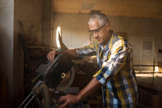 The carpenter uses a wood-cutting machine