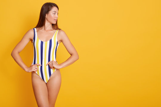Photo of young woman with straight dark hair dressed in swimsuit, looking aside isolated over yellow background in studio, keeps hjands on hips, copy space for advertismant or promotion text.