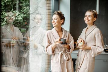 Women in bathrobes indoors