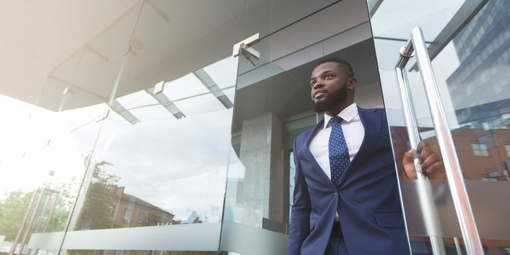 Young african job seeker leaving building after interview