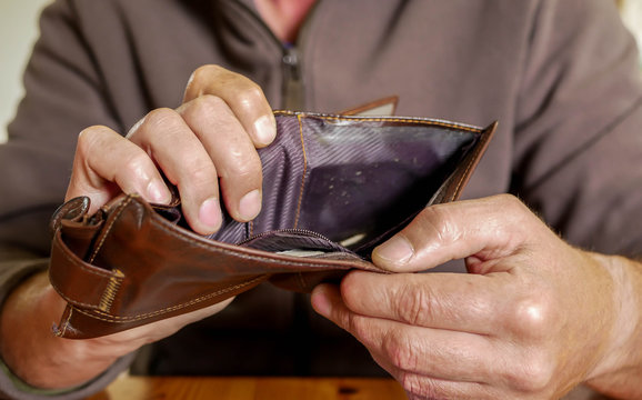 Caucasian worker  with a missing finger showing hes empty wallet, conceptual image of underpaid labour.
