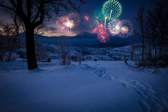New Years firework display in winter alpine mountain landscape.