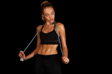 Fit Young Woman Holding Jump Rope Over Black Background