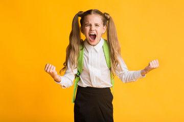Crazy Elementary School Girl Shouting Loudly Over Yellow Background