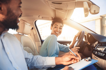 Happy woman in examination car, smiling to male instructor Wall mural