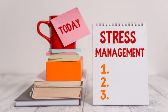 Word writing text Stress Management. Business photo showcasing method of limiting stress and its effects by learning ways Cup sticky note stacked note pads books square box spiral wooden table