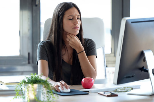 Illness young business woman with terrible throat pain working with computer in the office.