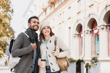 Beautiful happy couple autumn portrait. Young joyful smiling woman and man in a city in winter.  Love, travel, tourism, students concept