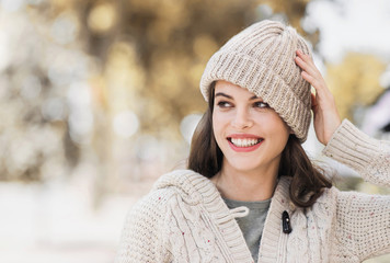 Beautiful joyful woman autumn portrait. Smiling girl wearing warm clothes and hat in a city in winter