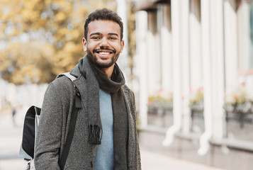 Handsome joyful man autumn portrait. Smiling men student wearing warm clothes in a city in winter