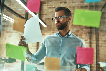 Creativity. Young and handsome bearded man in eyeglasses planning working process and using colorful stickers while standing in front of glass wall