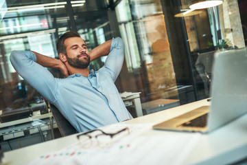 Work done Satisfied young bearded businessman leaning back with hands behind head and smiling while sitting in the modern office Fotoväggar