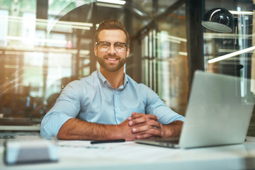 Great results Young bearded businessman in eyeglasses and formal wear looking at camera and smiling while sitting in the modern office Wall mural