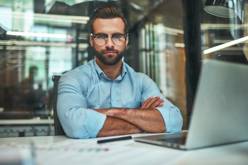 Confidence. Young bearded businessman in eyeglasses and formal wear looking at camera and keeping arms crossed while sitting in modern office Fotoväggar