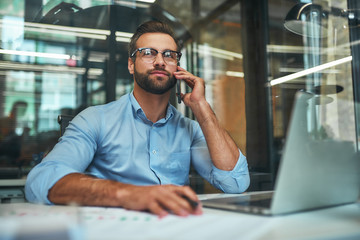 Happy to help you. Portrait of young handsome man in eyeglasses and formal wear talking on the phone with client while sitting in the office