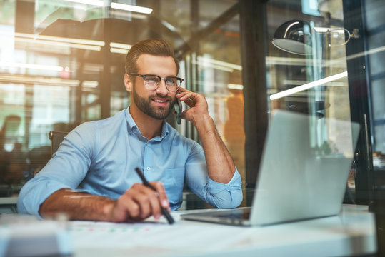 Customer support. Portrait of young and cheerful businessman in eyeglasses and formal wear talking on the phone and smiling while sitting in the office