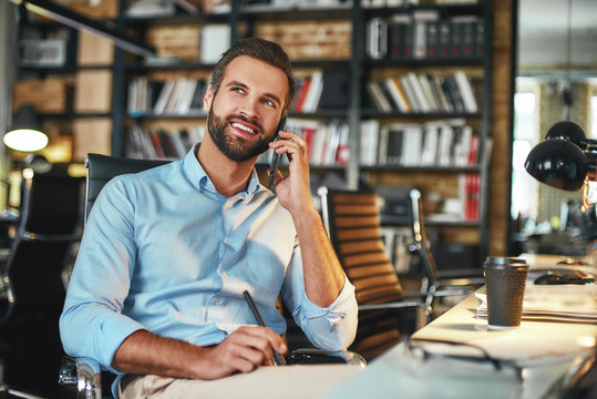 Happy to hear you Young bearded businessman in formal wear talking with client by phone and smiling while sitting in modern office