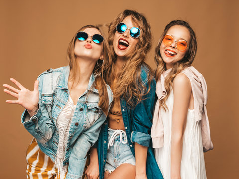 Three young beautiful smiling hipster girls in trendy summer casual clothes. Sexy carefree women posing on golden background. Positive models going crazy