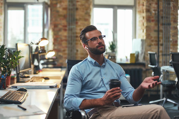 Always in touch. Portrait of young bearded man in eyeglasses and headphones talking with client and holding cup of coffee while sitting in the modern office