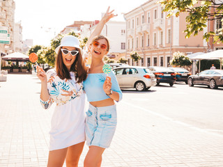 Two young beautiful smiling hipster girls in trendy summer clothes and panama hat.Sexy carefree...