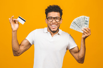 Handsome bearded african american man in casual holding stack of money and a credit card, he is happy winner with million dollars in his bank account.