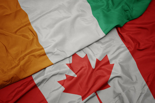 waving colorful flag of canada and national flag of cote divoire.