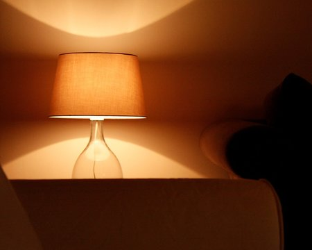Closeup of a lighted lamp near brown wall