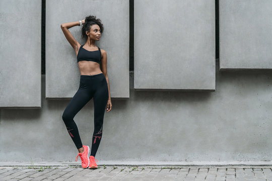 Full length of fit young woman in sports wear looking away standing outdoors
