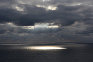 a sunbeam that sneaks through the clouds and goes to the sea in Cabo Raso, Portugal