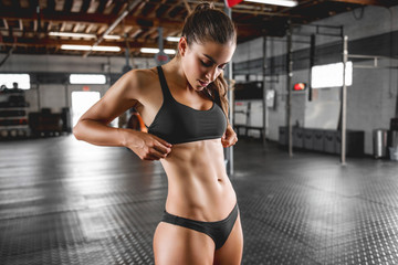 Healthy sports lifestyle. Athletic young woman in bikini sports clothing posing in gym Fototapete