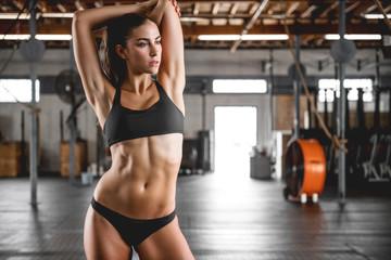 Sexy fitness woman with perfect body posing in black sports bikini in gym