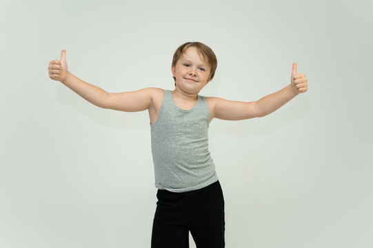 Photo is a waist-high portrait of a fun cheerful cute happy school-age athlete boy in a T-shirt. Rejoices, smiles on a white background. Shows hands.