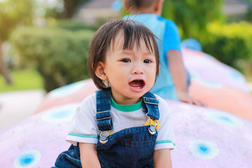 Portrait image of 1 years and 4 months olds baby girl. Asian child girl crying when she playing with the toy at the playground. Expression and emotions of baby concept.