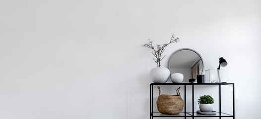 Single modern black display in front of white wall